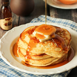 a pate of copycat cracker barrel buttermilk pancakes sits on a blue and white checked napkin. There is butter and maple syrup on the pancakes.