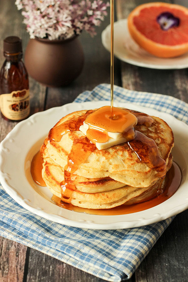 A lovely plate of copycat cracker barrel pancakes topped with syrup and butter. There is a vase of lilac in the background and half a grapefruit garnished with a pansy.