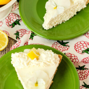 Two slices of lemonade icebox pie sit on green plates. They are garnished with a pansy and slice of lemon.