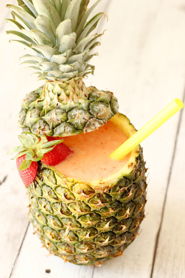 A pineapple is hollowed out and filled with cool, refreshing strawberry pina colada cocktail. There is a straw and a halved strawberry on the edge.