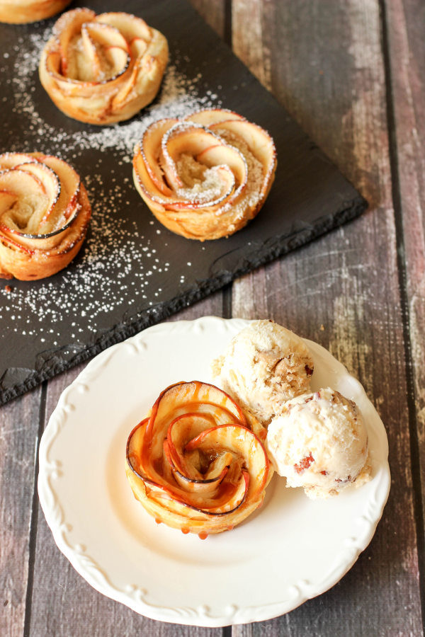 A beautiful apple pie rose sits on a white plate. There are scoops of ice cream on the side and a bit of caramel sauce drizzled over the top of the rose.