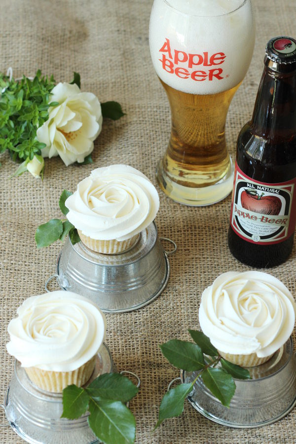 Table covered with burlap holds apple cupcakes frosted like white roses.  There is a glass of apple beer nearby and each cupcake sits on a miniature overturned tin bucket.