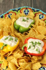 A big colorful platter is full of chips. Among the chips are three different colors of bell pepper and each pepper is cut in half and filled with a zesty, creamy Mexican dip. The dip is garnished with cilantro.