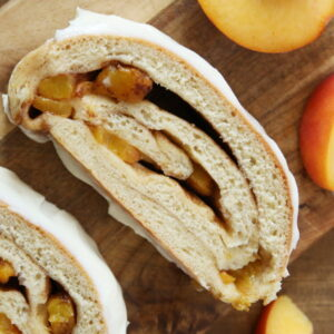 Two slices of cinnamon swirl peach bread are resting on a wooden cutting board. There is cream cheese glaze spread thickly on the top of the slices and some cut peaces around the bread.