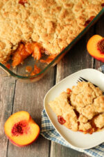 A big pan of easy peach cobbler has one slice cut out and plated on a white plate. Half a peach sits next to the dish.