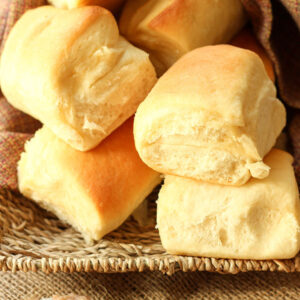 A basket is loaded up with big golden copycat Texas Roadhouse Rolls. Next to the rolls is a dish of cinnamon honey butter.