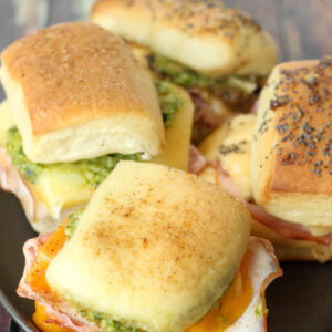 Four different hot ham and cheese sliders sit on a black plate. You can see ingredients like pesto and melted cheese and ham.