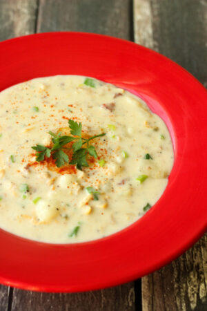 A bright red soup plate of clam chowder sits on a wooden table. The chowder is garnished with parsley and paprika.