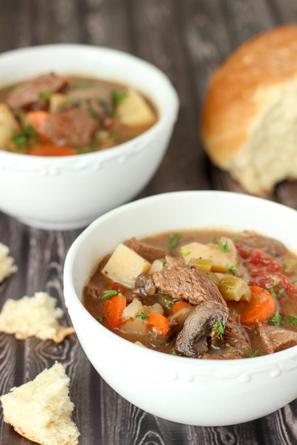 Two bowls of rich, filling beef stew sit on a table next to some torn bread. In the stew you see big chunks of beef, mushrooms, potatoes, carrots and some fresh parsley.