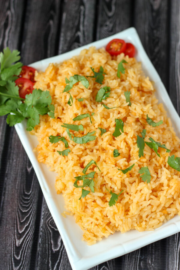 A white platter full of restaurant style Mexican rice sits on a dark wood table. There is a garnish of tomatoes and cilantro.