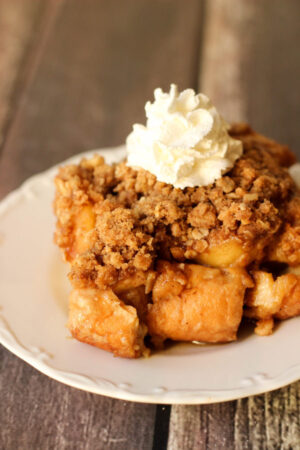 A big square of apple crisp French Toast casserole sits on a white plate. You can see a dollop of whipped cream on top.