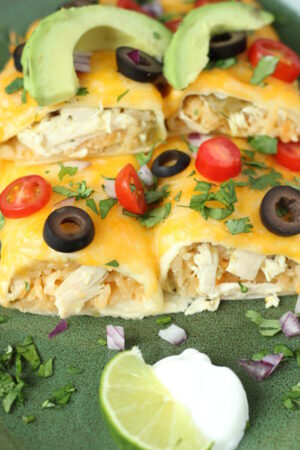Two chicken and rice enchiladas sit on a green plate. They are covered with cheese and olives and tomatoes. Slices of avocado sit on the top.