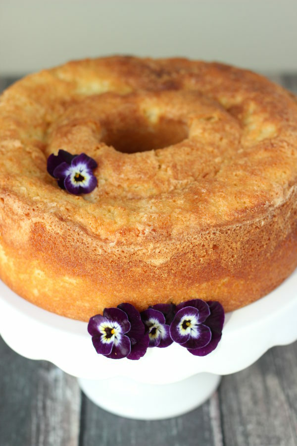 A beautiful pound cake sits on a white platter. There are purple pansies garnishing the cake.