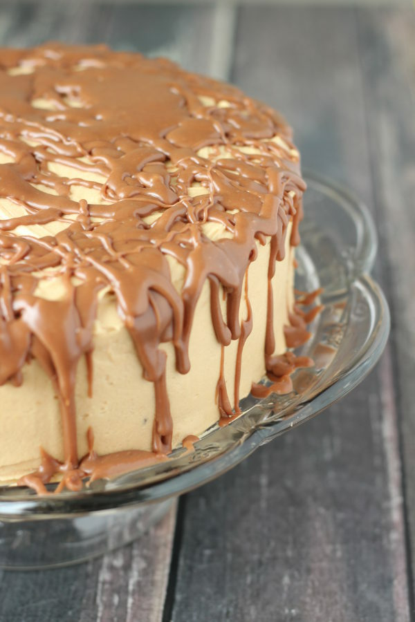 A chocolate cake covered with peanut butter frosting sits on a clear cake stand. The peanut butter frosting is covered with milk chocolate drizzle.