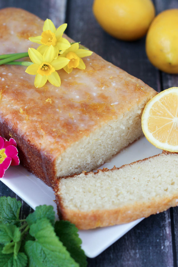 This drizzled lemon loaf is on a white plate. Fairy daffadills are on top and lemons and lemon balm garnish the loaf.