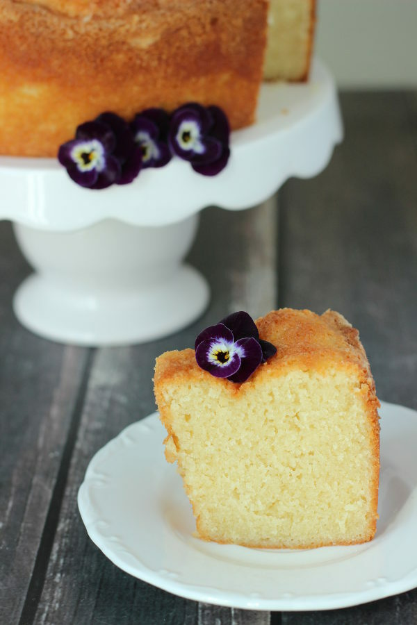 A large round pound cake sits on a white cake stand. A slice is cut out and sitting in front of the cake on a white plate. Pansies garnish both.