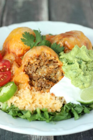 A platter of taco balls with all the fixings. There are three taco meatballs covered in cheese. They are plated with lettuce, rice, sour cream, guacamole, and tomatoes.