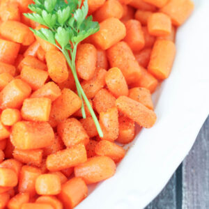 A large white casserole dish is full of roasted creole carrots. A sprig of parley is garnishing the top.