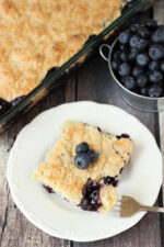 A white plate holds a big square of blueberry cobbler topped with a few fresh blueberries. In the background you see a cooked blueberry cobbler and a tin pail overflowing with blueberries!