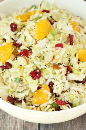 A big white bowl full of Asian coleslaw. You can see dried cranberries and mandarin oranges tucked in the shredded cabbage