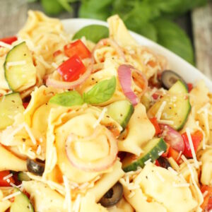A big bowl of tortellini pasta salad sits ready to eat next to some fresh herbs. You can see big cheese filled tortellini, diced bell peppers, pieces of cucumber, and sliced olives. The salad is garnished with Parmesan cheese.