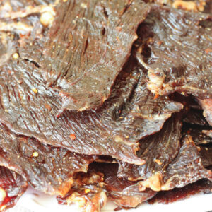 A big pile of strips of beef jerky are stacked on a white dinner plate. You can see black and red pepper on the jerky.