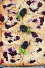 A big pan of blackberry cobbler sits waiting to be eaten. There are fresh blackberries and mint leaves on top.