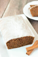 A fresh, tender loaf of carrot and zucchini spice bread sits on a white plate. The loaf is covered in apple cider glaze and sitting next to some cinnamon sticks. A plate of slices is ready to eat in the background.