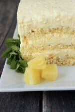 A simple pineapple cake sits on a white platter. There are three layers of pound cake and three layers of pineapple cream full of crushed pineapple. The plate is garnished with a sprig of mint and three chunks of pineapple.