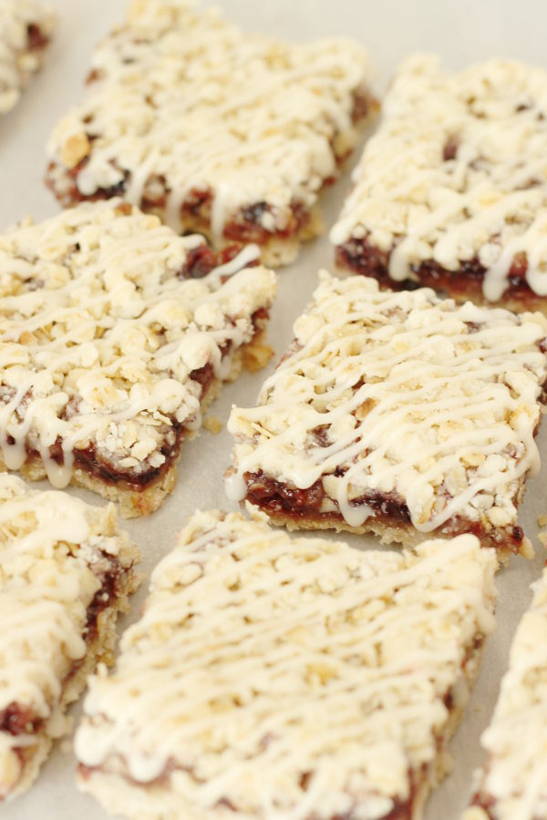 Berry crumb bars are laid out in two rows. The bars are square and have a crumb topping and icing drizzle.