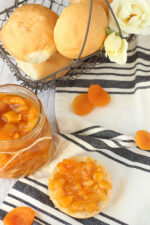 A fresh jar of dried apricot jam sits next to an English muffin slathered with jam. In the background a wire basked full of rolls and roses waits for a hungry guest.