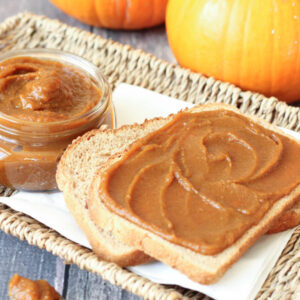 Slices of toast on a white platter are slathered with spicy homemade pumpkin butter. You can see pie pumpkins in the background and a mason jar with additional pumpkin butter.