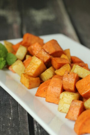 A white platter of roasted yams and sweet potatoes dusted with cinnamon. This healthy side dish looks appitizing.