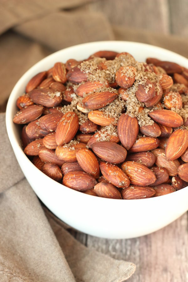 A big white bowl is full of fried almonds. You can see plenty of gray, smoked sea salt on the nuts.