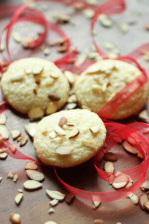 A wooden table has three almond cookies in the middle of it. There are slivered almonds scattered around and some gauzy red ribbon swirls.