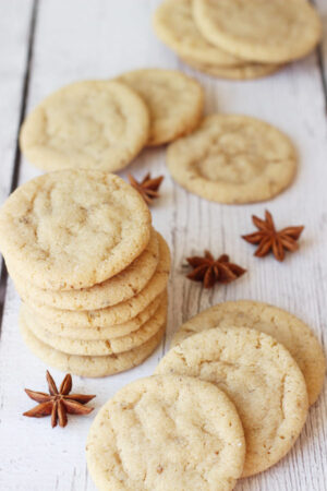 Lovely anise cookies are stacked and scattered over a white table. Some whole pods of anise are visible in the photo.