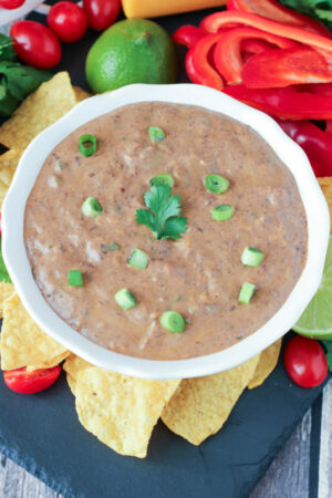 A white bowl of creamy black bean dip is garnished with green onions. It is surrounded by red peppers, cherry tomatoes, chips and wedges of lime.