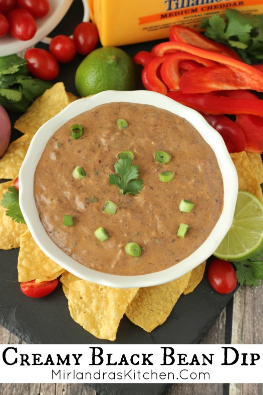 White bowl of black bean dip. Boil is surrounded by chips and veggies for dipping.