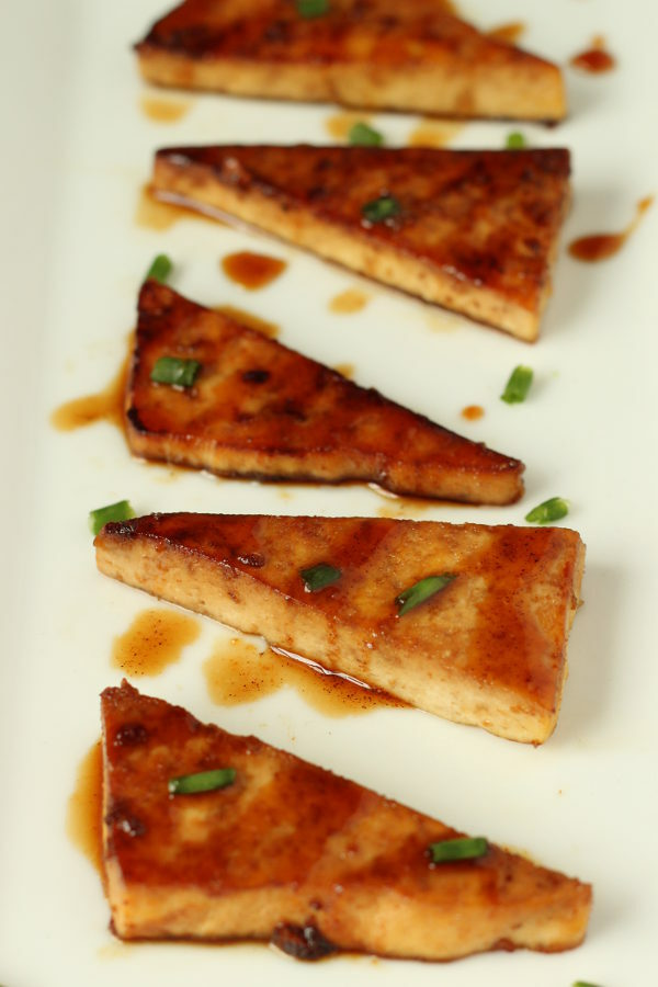 fried teriyaki tofu triangles are lined up on a white platter. There is a sprinkling of green onions garnishing it.