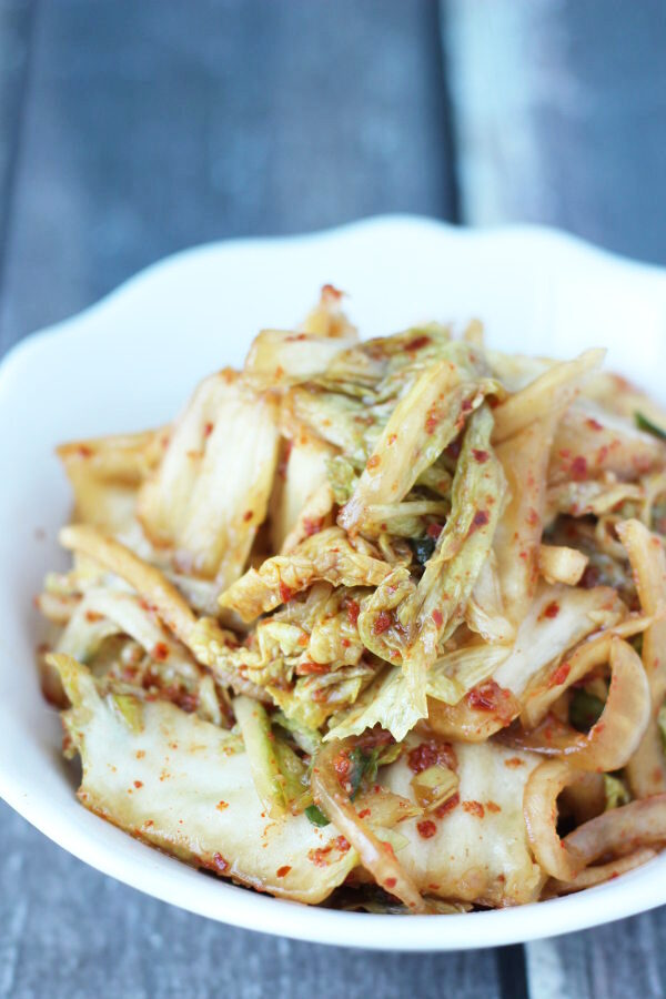 A white bowl of homemade kimchi. You can see slices of napa cabbage and the Korean red pepper flakes on the kimchi.