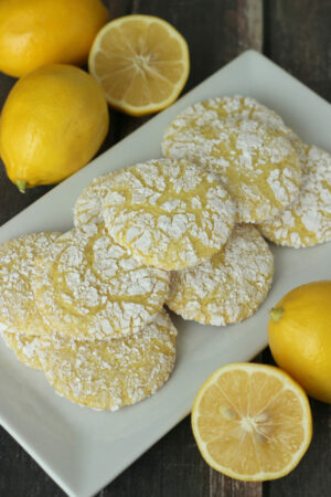 A square white platter is piled up with pretty lemon snowflake cookies. The cookies are yellow with a powdered sugar snowflake pattern on them. The platter is surrounded by lemons sitting on a wooden table.