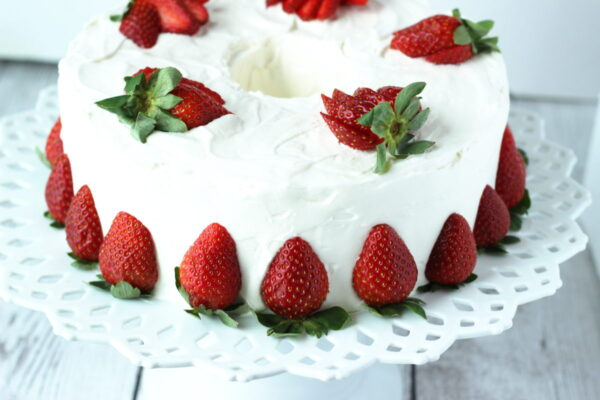 A pound cake is frosted with snow white whipped cream frosting. The cake is siting on an elegant white ceramic cake plate. There are cut strawberries around the base of the cake and sliced strawberries fanned out on top.