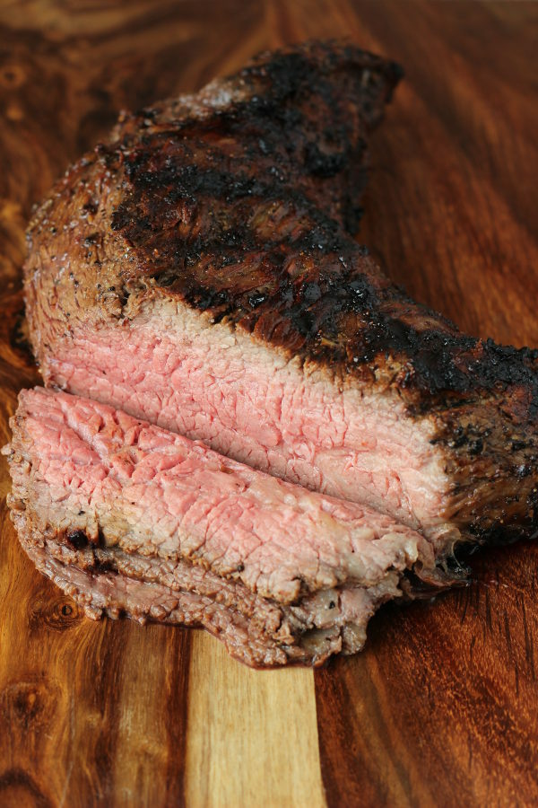 A cutting board has a grilled tri tip with slices off of one end.