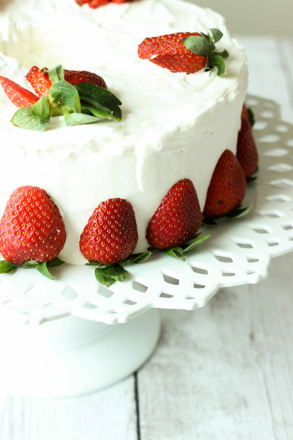 A stunning cake sits on decorative white cake stand. The cake is simple frosted with whipped cream frosting and decorated with fresh strawberries sliced or cut in half.