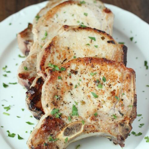 a large white platter has four big pork chops on it. Each chop is perfectly golden. There is a sprinkling of parsley on top.