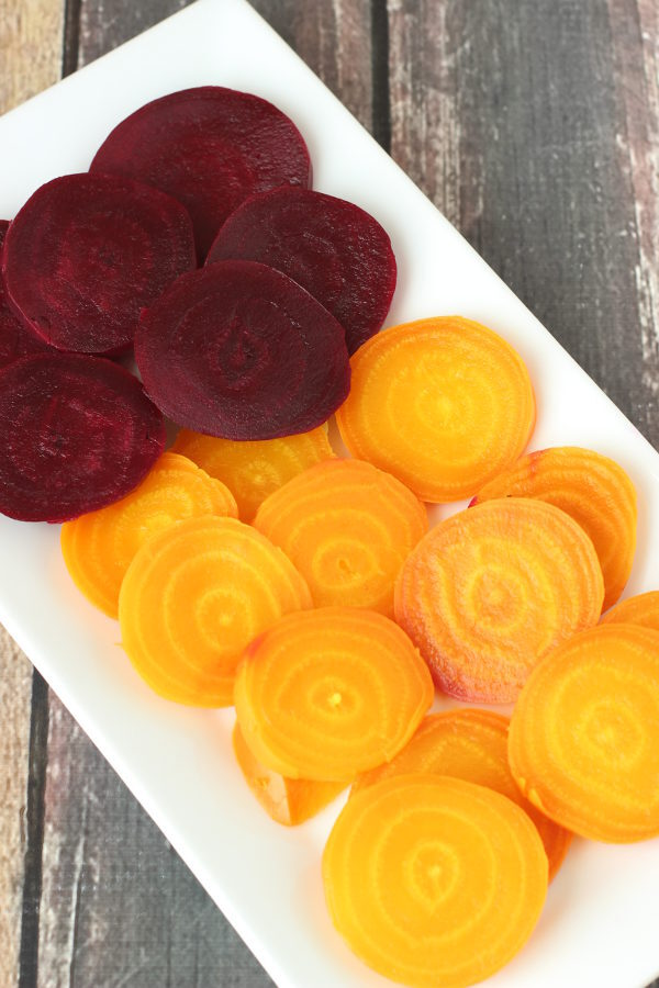 A white rectangular platter is filled with lovely sliced beets. The top of the platter holds slices of purple beets while the bottom holds slices of golden beets. These are soft from being cooked in the Instant pot.