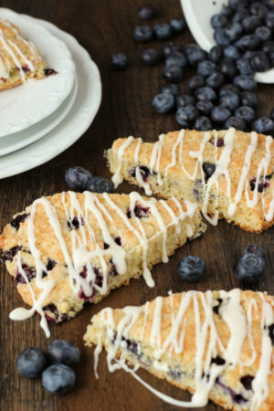 Three fresh blueberry scones sit on a table next to a stack of white plates. A pile of blueberries is spilling out of a dish among the scones.