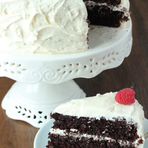 A chocolate cake sits on a white cake stand. The cake is frosted with vanilla buttercream.