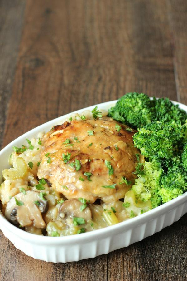 A white dish is full of creamy chicken and rice casserole. You can see bites of mushrooms and celery in the rice. There is a side of broccoli on the dish.