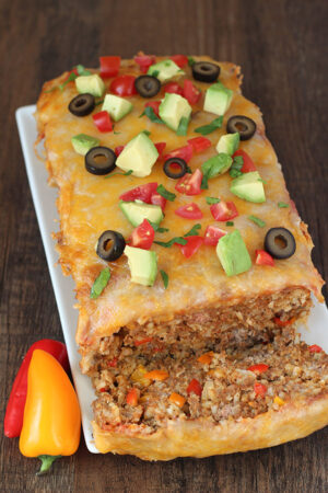 A big Mexican meatloaf sits on a white platter. The first slice has been cut off and you can see a thick layer of cheese on top of a rich meatloaf studded with chunks of bell peppers and plenty of rice.